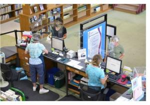 Library staff help patrons check out books at the circulation desk.